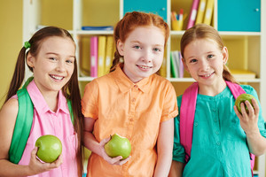 Happy schoolgirls with green apples looking at camera