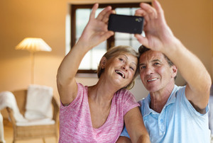 Happy senior couple taking selfie in their living room.