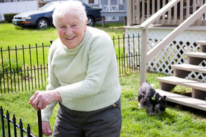 Happy senior lady in backyard with her dog