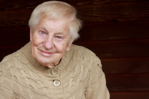 Happy senior lady in beige sweater smiling