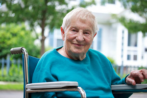 Happy senior lady in wheelchair relaxing outside