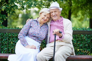 Happy seniors sitting on bench and having rest in the park