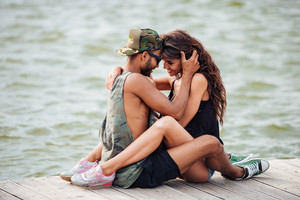 Happy sensual young couple sitting and hugging on pier