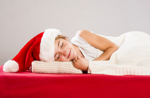 Happy small girl in santa hat with christmas gift, lying on the bed