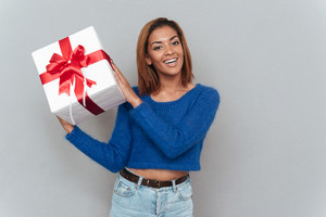 Happy smiling african woman in sweater and jeans holding white gift with red tape from the right. Isolated gray background