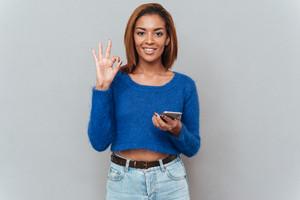 Happy smiling african woman in sweater and jeans with phone showing ok sign. Isolated gray background