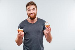 Happy smiling bearded man eating cream cake isolated on white background