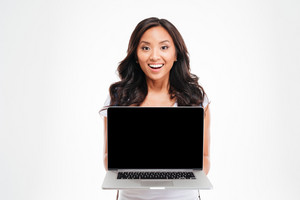 Happy smiling beautiful asian woman holding laptop with blank screen isolated on a white background