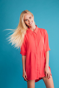 Happy smiling blonde woman in red dress standing with flying hair isolated on a blue background