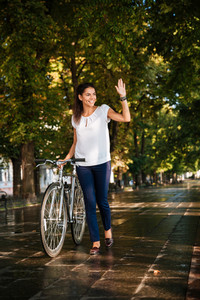 Happy smiling girl waving hand with bicycle at park