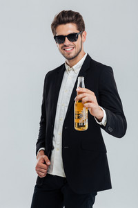 Happy smiling man in black suit holding beer bottle over grey background