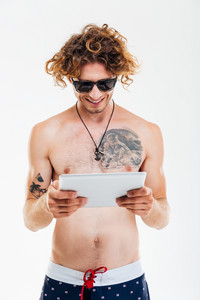 Happy smiling man in sunglasses and beach shorts using pc tablet isolated over white background