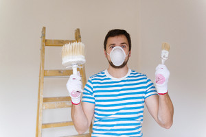 Happy smiling man painting the walls of new home with paintbrush while wearing respiratory safety equipment
