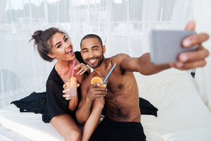 Happy smiling multiracial couple making selfie and holding cocktails at the beach
