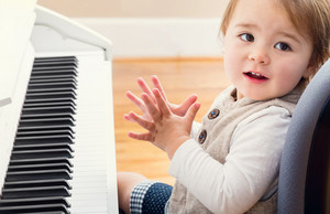 Happy smiling toddler girl excited to play piano