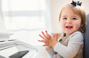 Happy smiling toddler girl excited to play the piano