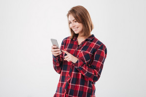 Happy smiling woman in plaid shirt using smartphone over white background
