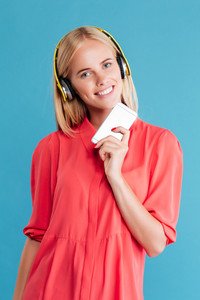 Happy smiling woman in red dress with headphones holding mobile phone isolated on the blue background