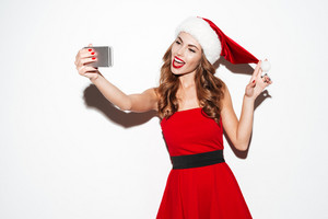 Happy smiling woman in red santa claus costume making selfie using her cellphone over white background