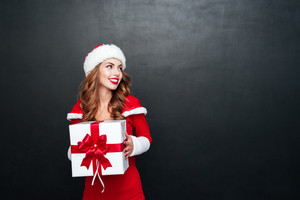 Happy smiling woman in red sants claus outfit holding big xmas present isolated on the black background