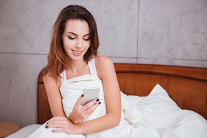Happy smiling woman using smartphone on the bed at home