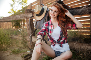 Happy smiling young redhead cowgirl resting at the ranch fence