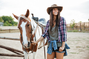 Happy smiling young woman in cowboy hat with her horse at the farm