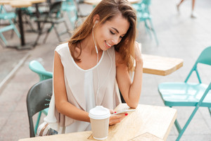 Happy smiling young woman with earphones listen music and typing message on smartphone at cafe