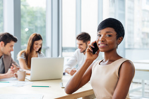 Happy successful african young businesswoman talking on cell phone while working with her business team