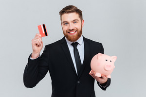 Happy succsessful business man in suit holding piggy bank and credit card in hands. Isolated gray background