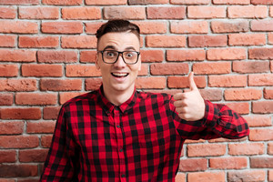 Happy surprised Hipster in glasses standing near the wall with thumb up and looking at camera