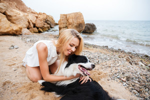 Happy tender young woman hugging her dog and smiling on the beach