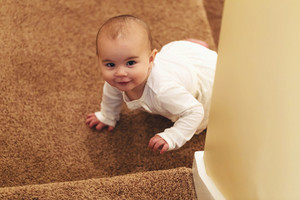 Happy toddler girl climbing up the stairs in her house