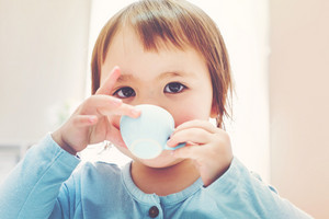 Happy toddler girl drinking from a tiny teacup