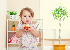 Happy toddler girl eating an apple inside her house