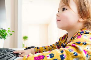 Happy toddler girl enjoying using her computer