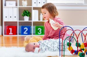 Happy toddler girl feeding her newborn baby sister a bottle