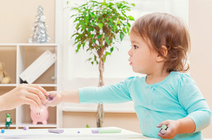 Happy toddler girl handing chalk to an adult inside her house