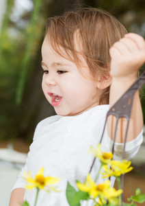Happy toddler girl happily playing outside with flower pots