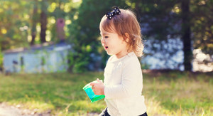 Happy toddler girl happily playing outside