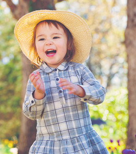 Happy toddler girl in a hat playing outside