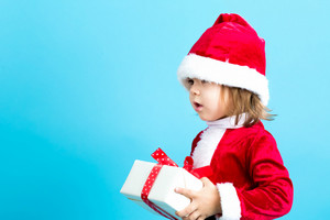 Happy toddler girl in a Santa costume with a gift box