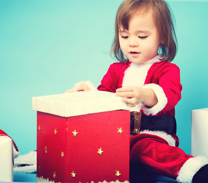Happy toddler girl in a Santa costume with gift boxes