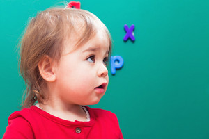 Happy toddler girl in front of a green chalkboard
