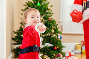 Happy toddler girl interacting with Santa Claus by the Christmas tree