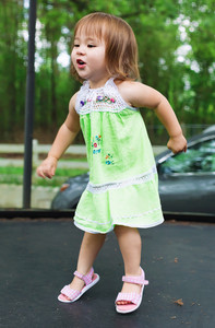 Happy toddler girl jumping on a big trampoline