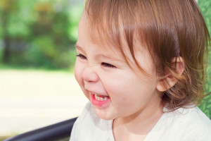 Happy toddler girl laughing while playing on a swing outside
