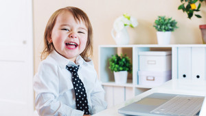 Happy toddler girl laughing while using her laptop