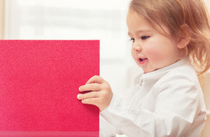 Happy toddler girl opening a big red binder