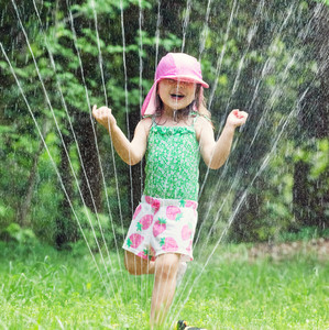 Happy toddler girl playing in a sprinkler on a hot summer day